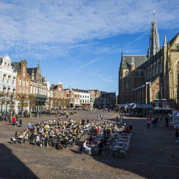 Haarlem – Het zonnige weer op deze tweede kamerverkiezingsdag zorgt ervoor dat de terrasjes op de Grote Markt druk worden bezocht. Veel mensen genieten van de zon en de lekkere voorjaarswarmte met een lekker drankje op het terras.